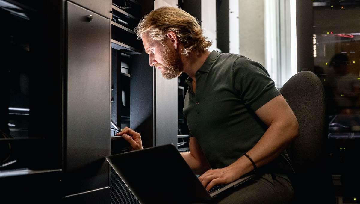 Man holding laptop examines data server