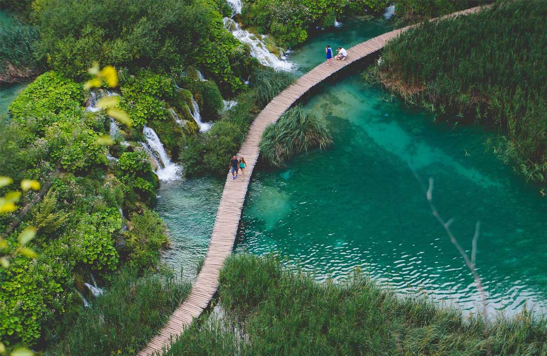 Couples walk across long bridge over blue water