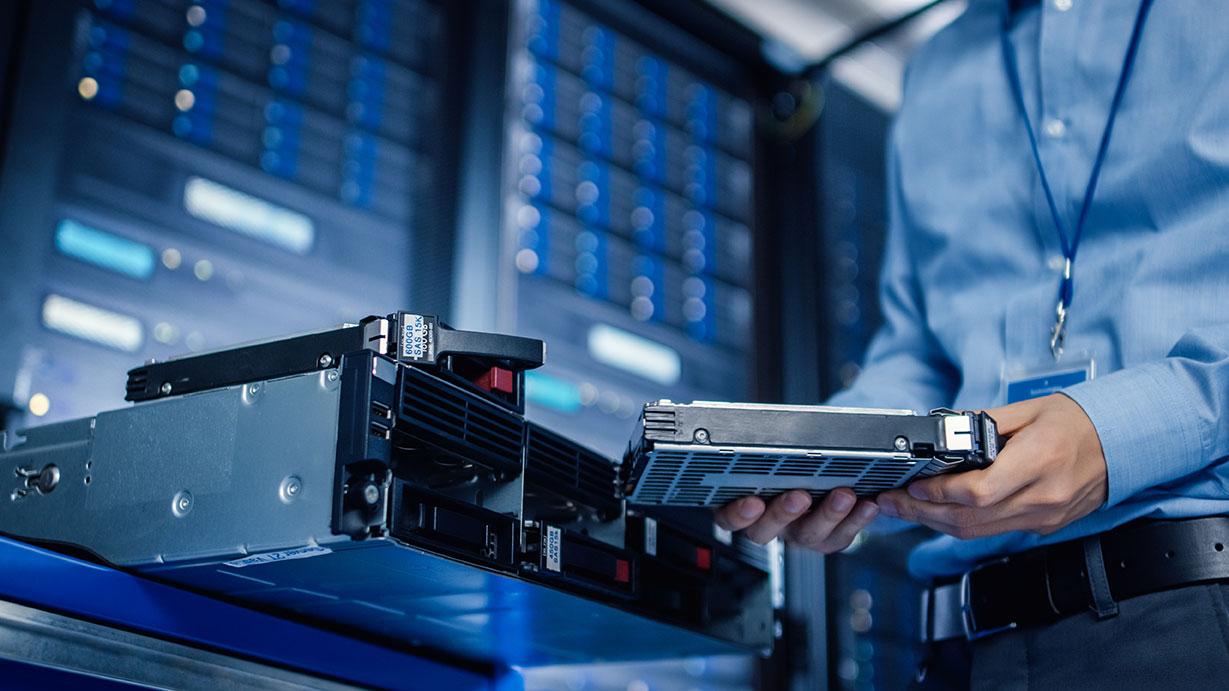 IT Engineer Installing Hardware Equipment into Server Rack
