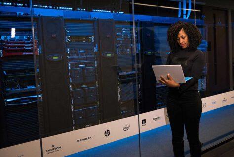 Woman working on laptop near modern looking data center servers